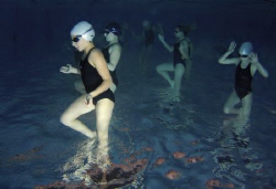 Aliens.  Training of a group of young synchro swimmers in... by Alena Vorackova