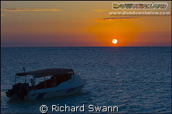 Sunrise over our dive boat, Lankayan island Sabah Borneo.... by Richard Swann