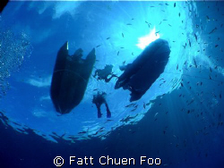 Divers surfacing after a dive in the crystal clear waters... by Fatt Chuen Foo