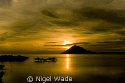 Sunset over Manado Tua. Pure Gold. by Nigel Wade