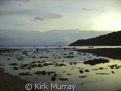 Walking boats out to sea at low tide, Perhentian Islands,... by Kirk Murray