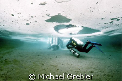 Ice divers, using cave dive techniques, proceeding to the... by Michael Grebler
