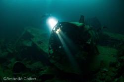 Diver shines his light through a Zero Fighter Plane insid... by Amanda Cotton