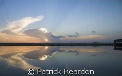 The sunset is reflected in the calm waters of an inlet on... by Patrick Reardon