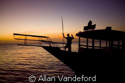 The staff returns a dive vessel at days end.  The sunset ... by Allan Vandeford