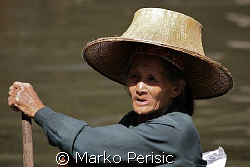 Portrait of a fisher woman making her way in a dug out boat. by Marko Perisic