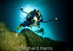 Photographers. Divers swimming into a sea cave in the Poo... by Richard Harris