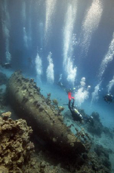 Divers (and bubbles) over the wreck in Abu Galawa. by Dray Van Beeck