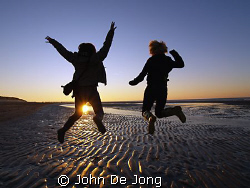 Jump.  My doughter Kim and hier friend Manon at the bea... by John De Jong
