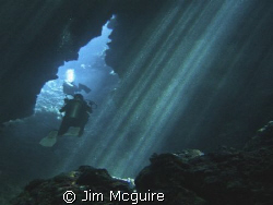 Divers exiting the cave that leads to Mirror Pond (one of... by Jim Mcguire