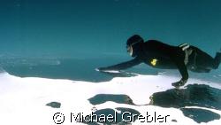 Apnea Diver under ice, Morrisons Quarry, Quebec, Canada. ... by Michael Grebler