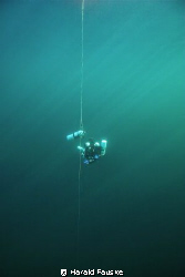 Technical diver at deco stop in crystal clear water by Harald Fauske