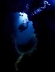 Descending through the chimney at Sail Rock, Gulf of Thai... by Soren Egeberg