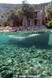A sunken fishing boat in shallow waters in Pelion. by Vasilis Lekkas