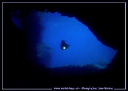 Caroline my wife entering a cave on Gozo Island in Malta.... by Michel Lonfat