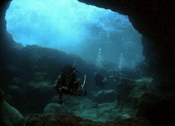 A couple of friends entering a cave. by Juan Torres