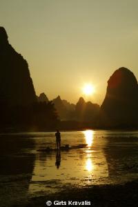 Fisherman on Li River by Girts Kravalis