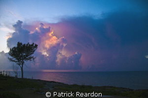 The setting sun lights up afternoon thunderheads on Grand... by Patrick Reardon