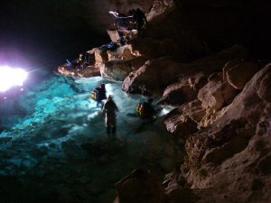 Divers get ready in the main chamber in Weebubbie Cave, n... by Mick Tait