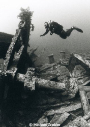 At a depth of 90 feet, a diver investigates the steering ... by Michael Grebler