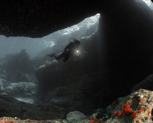 Different saturation levels of this diver inside a cave. by Juan Torres