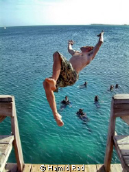My buddy Simon doing a backflip from the Utila Dive Cente... by Hamid Rad