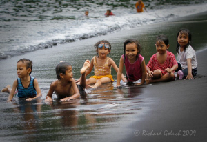 Lembeh Strait-Local kids playing on black sand beach. by Richard Goluch