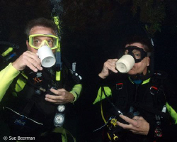 Two divers enjoying their morning coffee at the Halliburt... by Susan Beerman