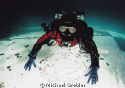 Technical diver on ice. Posed upside-down under the ice i... by Michael Grebler