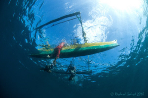 Lembeh-Local kids swimming next to father's canoe by Richard Goluch