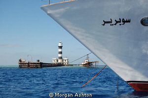 Daedalus Reef Lighthouse and the bow of the Emperor Super... by Morgan Ashton