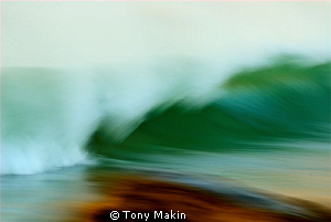Breaking wave. Taken by panning with a slow shutter speed... by Tony Makin