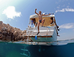 kid jumping from the boat by Andy Kutsch