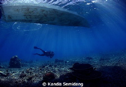 A diver passing under a boat by Kandis Semidang