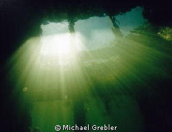 Looking up at the light beams coming through the fisherme... by Michael Grebler