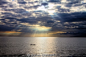 A lone canoe tried to beat the sunset in Maui. by Rylan Stewart