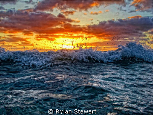 A wave starts to break as the sun sets near Waikiki, HI by Rylan Stewart