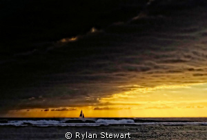 A lone sailboat outruns an impending storm in the waters ... by Rylan Stewart