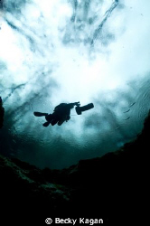 Cave Diver on a DPV gets ready to descend into the moulth... by Becky Kagan
