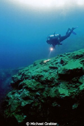 A diver approaches the crest of the vertical drop in Morr... by Michael Grebler