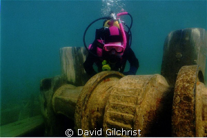 Young diver examines the windlass of the Schooner 'Sweeps... by David Gilchrist
