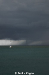 A larger water spout makes its way towards our boat in th... by Becky Kagan