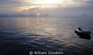 Sunrise from the Sun Dancer off Terneffe Atoll. by William Goodwin