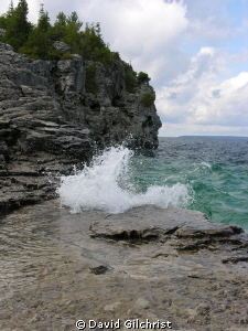 With the Limestone cliffs in the background, a wave 'cras... by David Gilchrist
