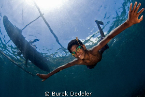 A young boy free diving from his dug out canoe with home ... by Burak Dedeler