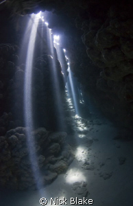 Lighting the way. Sun rays at Jackfish alley caves. by Nick Blake