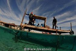 A group of divers on the jetty of Marsa Shagra Eco Villag... by Blaza Jovanovic