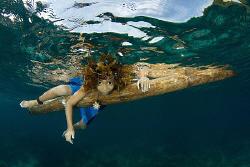 This is JenJen, a happy kid from Apo Island paddling arou... by Steve De Neef