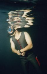 A dive instructor keeps an eye on his novice Open Water s... by Michael Grebler