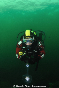 Diver investigating a jelly by Henrik Gram Rasmussen